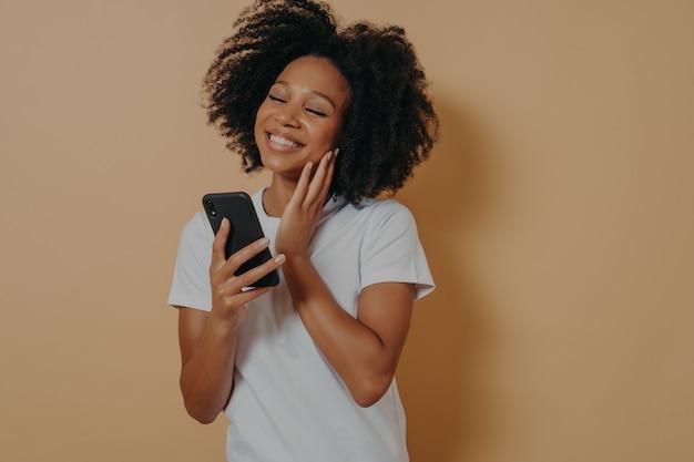Mooie jonge afro-amerikaanse vrouw met moderne smartphone in handen die blij is om een bericht van haar vriendje te krijgen, naar het scherm van het apparaat kijkt en glimlacht terwijl ze over een beige studiomuur staat