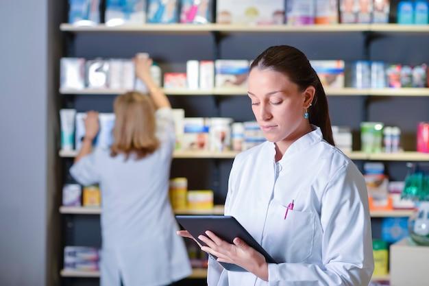 Mooie jonge apotheker die zich naast geneeskundeplanken bevindt, die tablet houden