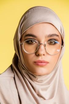 Mooie jonge arabische vrouw in stijlvolle hijab geïsoleerd op gele achtergrond met copyspace