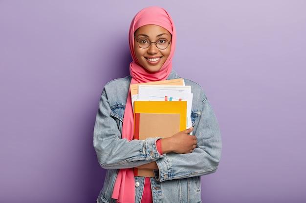 Mooie jonge arabische vrouw met donkere huid, draagt doorzichtige bril, houdt papieren en blocnote, heeft brede glimlach