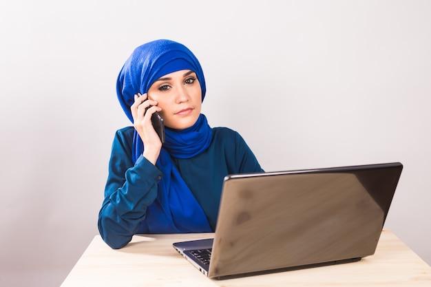 Mooie jonge arabische vrouw praten over de mobiele telefoon op witte achtergrond