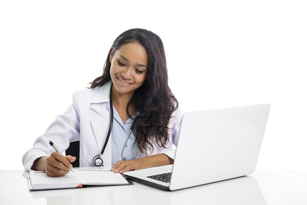 Mooie jonge arts die aan haar laptop werkt en op nota schrijft