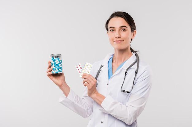 Mooie jonge arts in whitecoat die je een fles pillen en blaren met tabletten laat zien terwijl hij geïsoleerd voor de camera staat