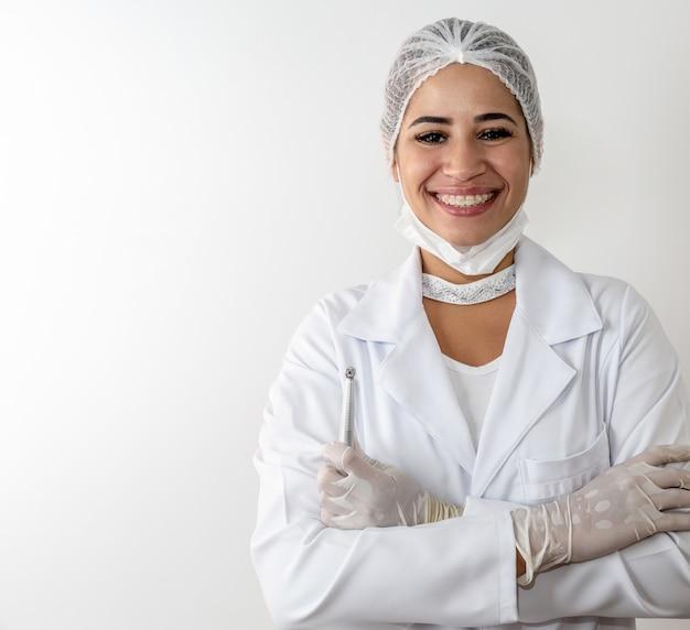 Mooie jonge artsenvrouw in medische witte laag en een beschermende masker en een spuit.