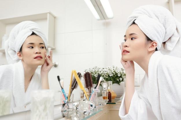 Mooie jonge asain-vrouw in badjas die naar badkamerspiegel kijkt en porieverfijnende toner aanbrengt