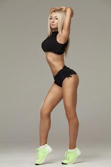 Mooie jonge atletische fitness model meisje poseren in studio op een grijze achtergrond