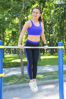 Mooie jonge atletische vrouw doet gymnastiek op haar handen op de balk