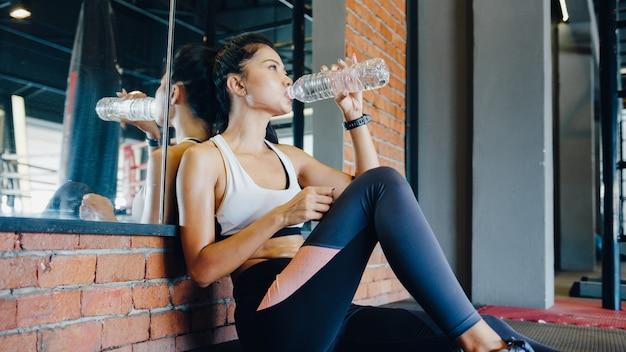 Mooie jonge aziatische dame drinkwater na vetverbranding training in fitness klasse