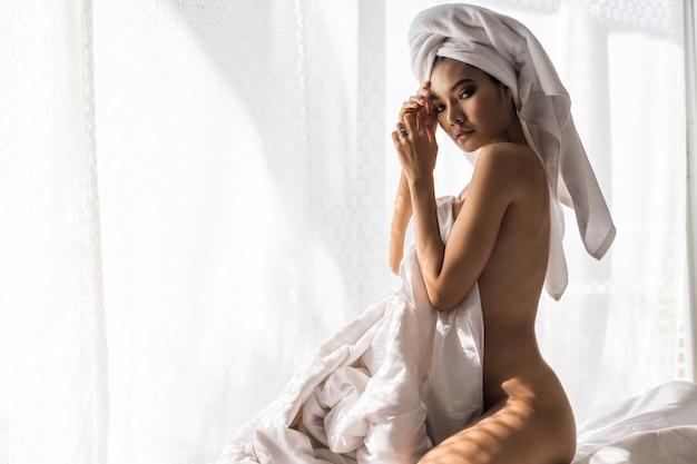 Mooie jonge aziatische die in douchehanddoek naakt op bed met deken wordt verpakt om lichaam dichtbij venster met natuurlijk licht door gordijn te bedekken. sexy naakt tan meisje na het nemen van een bad.