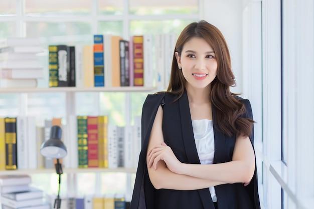 Mooie jonge aziatische kantoormedewerker glimlachend gelukkig staande met haar gekruiste armen