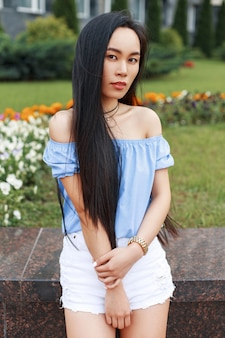 Mooie jonge aziatische meisje in een zomer blauwe blouse en witte korte broek is poseren in de buurt van het steegje van bloemen.