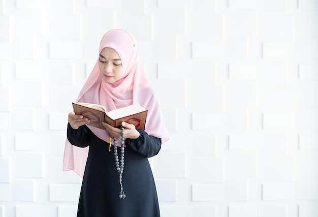 Mooie jonge aziatische moslim quran vrouwenlezing
