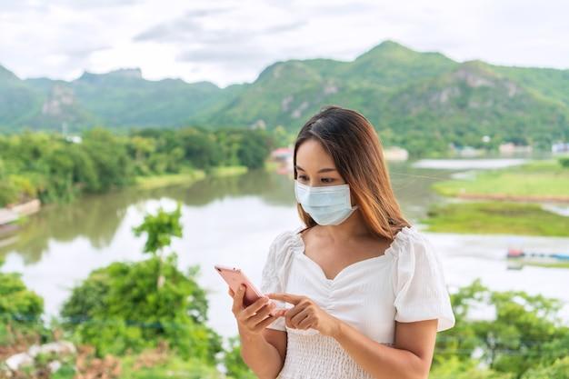Mooie jonge aziatische reizigersvrouw die beschermend gezichtsmasker draagt in openbare ruimte als gevolg van het verminderen van de verspreiding van covid 19, nieuwe normale levensstijl, reisconcept