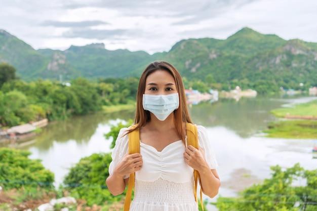 Mooie jonge aziatische reizigersvrouw die beschermend gezichtsmasker in openbare plaats draagt wegens het verminderen van de verspreiding van covid 19, nieuwe normale levensstijl, reisconcept