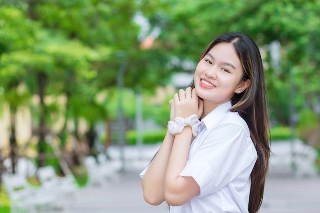 Mooie jonge aziatische studente met blond lang haar glimlacht en kijkt naar de camera terwijl ze handen vasthoudt en op de universiteit staat met een buitenboomachtergrond.