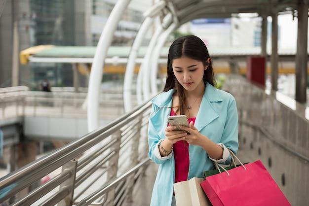 Mooie jonge aziatische toeristenvrouw chat en blader door de kaart met 5g-gegevens op smartphone om in de winter een winkelcentrum en reislocatie in een buitenlandse stedelijke stad te vinden. technologievoordeel voor reizigers over de hele wereld.
