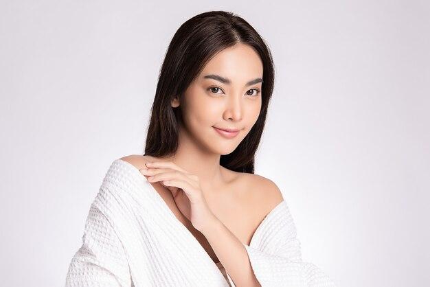Mooie jonge aziatische vrouw aan te raken haar lichaam met verse gezonde huid, geïsoleerd op een witte muur, schoonheid cosmetica en gezichtsbehandeling concept.