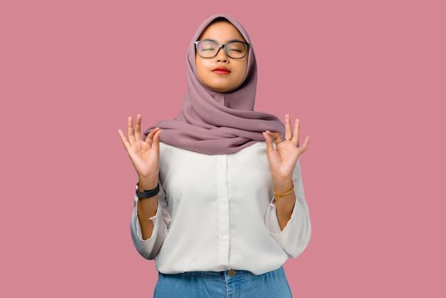 Mooie jonge aziatische vrouw ademt adem op roze achtergrond