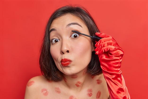 Mooie jonge aziatische vrouw brengt mascara op wimpers aan en maakt dagelijkse make-up zich voorbereidt op date of feeststands met blote lichaam tegen levendige rode muur