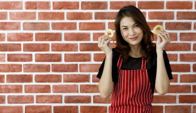 Mooie jonge aziatische vrouw chef-kok in rood gestreepte schort staan in de buurt van bakstenen muur en grappig grapje om uienring te laten zien met een glimlach voor het braden op zwarte pan op tafel met keukengerei en ingrediënten