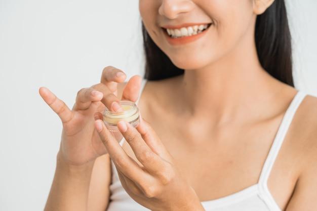 Mooie jonge aziatische vrouw cosmetische crème op haar gezicht toe te passen. lippenbalsem