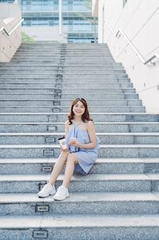 Mooie jonge aziatische vrouw die aan de buitentrap zit en smartphone gebruikt. levensstijl van moderne vrouw.