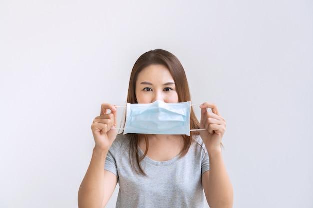 Mooie jonge aziatische vrouw die beschermend gezichtsmasker houdt
