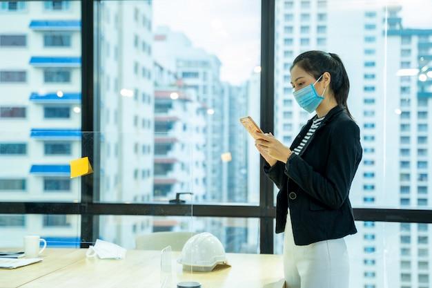 Mooie jonge aziatische vrouw die beschermend masker draagt om tegen covid-19 te beschermen die in bureau in modern bureau werkt.