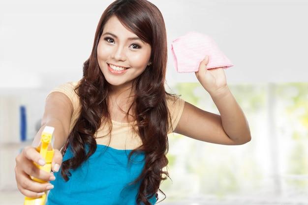 Mooie jonge aziatische vrouw die binnenlandse karweien doet, die nevel houdt