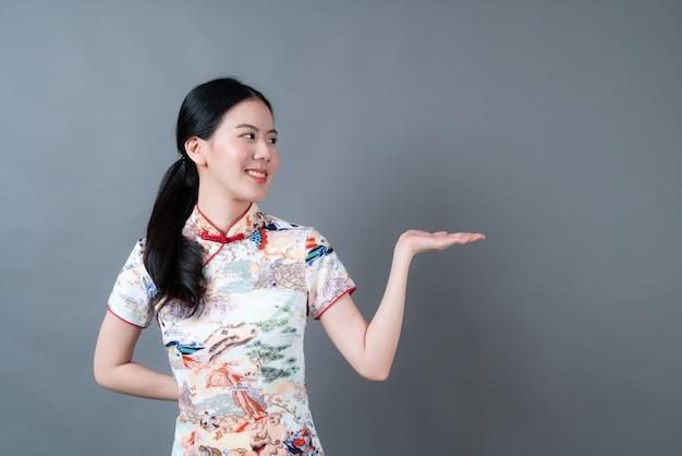 Mooie jonge aziatische vrouw die chinese traditionele kleding draagt met hand die aan kant in grijs voorstelt
