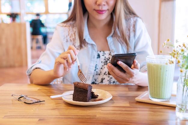 Mooie jonge aziatische vrouw die chocoladetaart eet tijdens het gebruik van smartphone