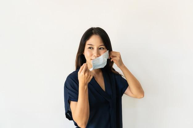 Mooie jonge aziatische vrouw die een medisch gezichtsmasker draagt voordat ze het huis verlaat. nieuw normaal, gezondheidszorgconcept. ruimte kopiëren