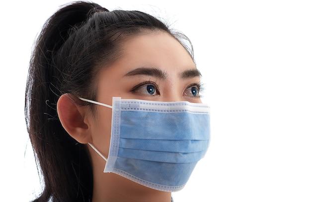 Mooie jonge aziatische vrouw die een medisch masker opzet