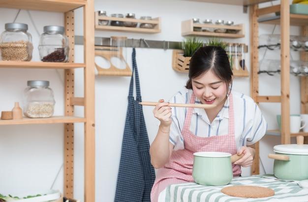 Mooie jonge aziatische vrouw die en soepvoedsel in de keuken koken testen