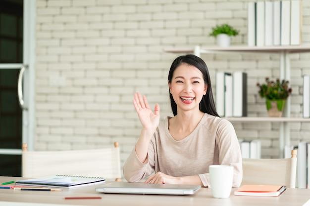 Mooie jonge aziatische vrouw die gelukkig glimlacht en naar de camera kijkt en hallo of hallo zegt en lacht met een vrolijke uitdrukking