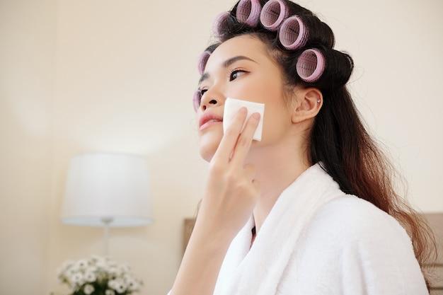 Mooie jonge aziatische vrouw die haar gezicht afveegt met wattenschijfje gedrenkt in micellair water bij het verwijderen van make-up