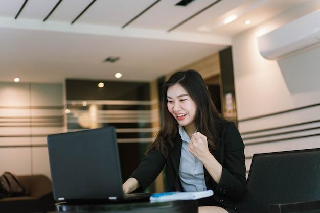 Mooie jonge aziatische vrouw die haar laptop met behulp van