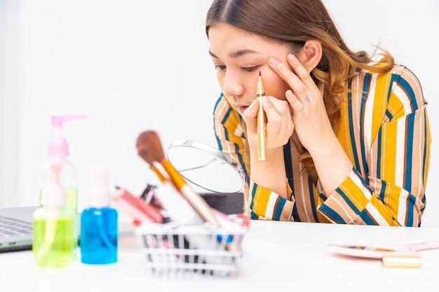 Mooie jonge aziatische vrouw die haar make-up op