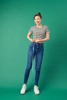 Mooie jonge aziatische vrouw die haar taille met een maatregelenband meet over groen