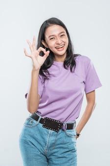 Mooie jonge aziatische vrouw die hand opheft en ok teken toont