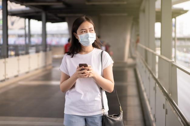 Mooie jonge aziatische vrouw die het beschermende masker draagt tijdens het reizen in de stad waar volledig met luchtverontreiniging pm2.5. ongezond stedelijk luchtverontreinigingsprobleem en coronavirusziekte in azië.