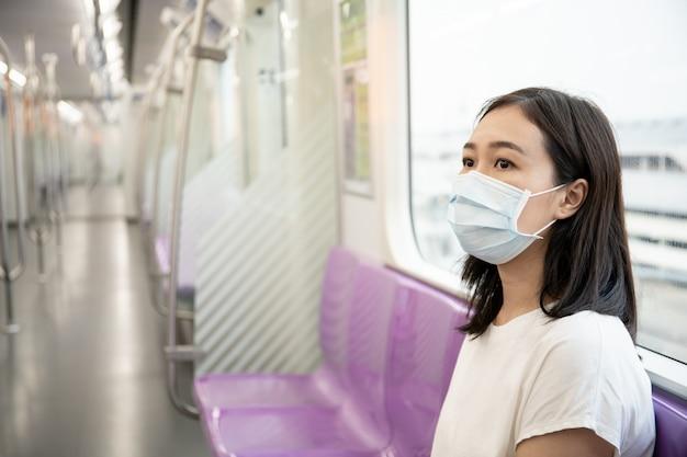 Mooie jonge aziatische vrouw die het beschermende masker draagt tijdens het reizen in de stad waar volledig met luchtverontreiniging pm2.5. wereldkritieke ziekte van covid19
