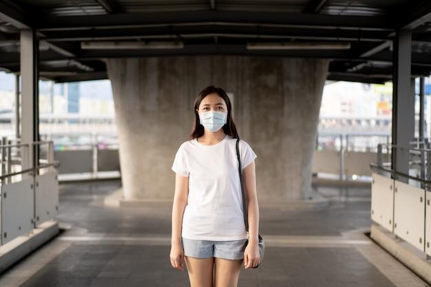 Mooie jonge aziatische vrouw die het beschermende masker draagt tijdens het reizen in de stad