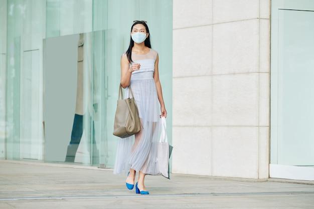 Mooie jonge aziatische vrouw die in medisch masker onderaan lege stadsstraat loopt