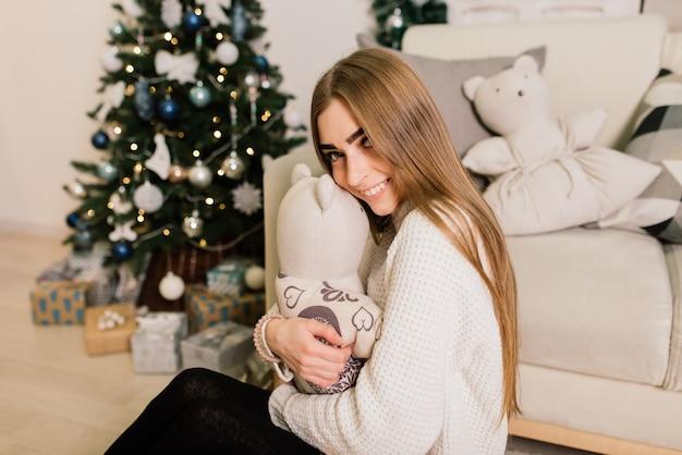 Mooie jonge aziatische vrouw die kerstmis thuis viert, die pret heeft tijdens het openen van cadeautjes