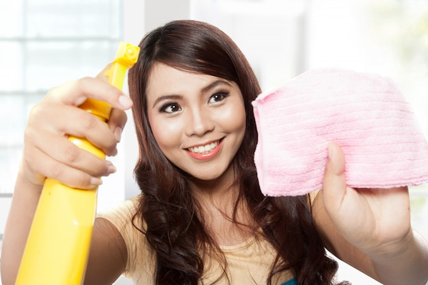 Mooie jonge aziatische vrouw die klusjes doen, die spuitbus en pi houden