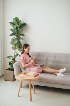 Mooie jonge aziatische vrouw die laptop gebruikt terwijl ze in de woonkamer zit en koffie drinkt