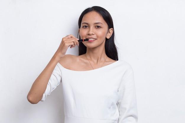 Mooie jonge aziatische vrouw die lippenstift gebruikt die op witte achtergrond wordt geïsoleerd