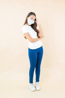 Mooie jonge aziatische vrouw die met gezichtsmasker op beige denkt