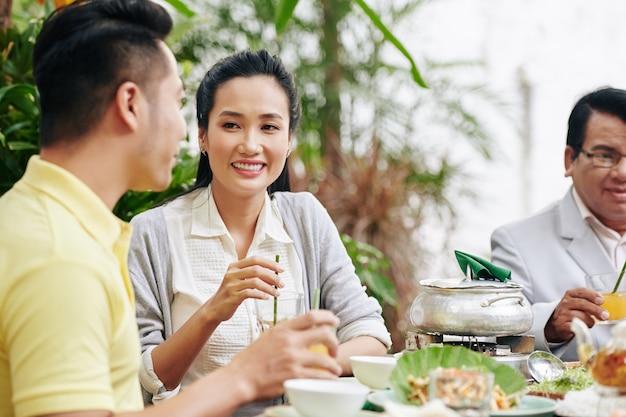 Mooie jonge aziatische vrouw die met haar man praat tijdens het familiediner